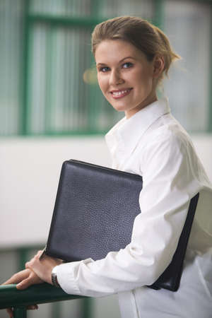 Pretty girl with the folder in her hands and man sitting at the table and signing the document photo