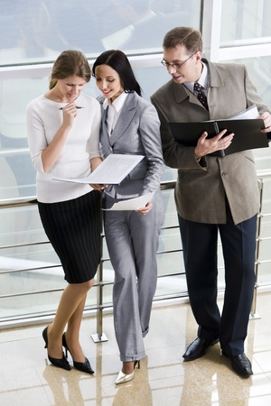 Smiling Hispanic businesswoman giving advices to her colleague and curious businessman in eyeglasses with opened paper case in his hands  photo
