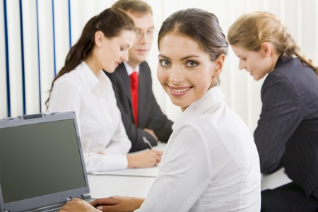 Young successful smiling woman sitting at the table on the background of three business people Stock Photo - 8357427