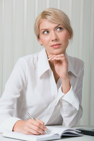 Portrait of beautiful dreaming woman in the office photo