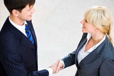 Photo of confident man and woman shaking hands making an agreement photo
