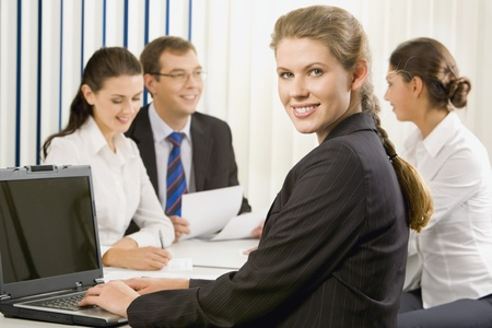 Attractive woman is sitting at the table and typing in the office on the background of her colleagues photo