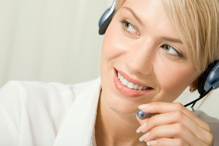 support agent: Portrait of friendly smiling telephone operator holding headset Stock Photo