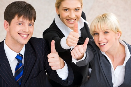 Portrait of three business people showing a sign of okay photo