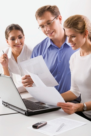 Team of three business people looking at the papers in the office photo