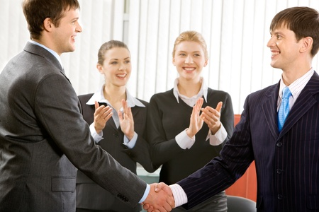 Image of two successful men making an agreement on the  background of applauding women photo