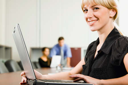 Young successful business woman sitting at the large table in boardroom photo