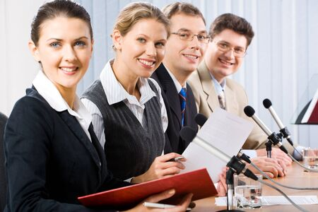 Portrait of four confident professionals sitting at the table and looking at camera photo