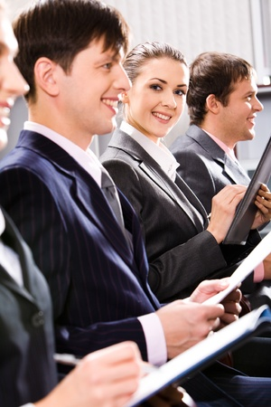 Portrait of smiling students sitting in row at a seminar  photo