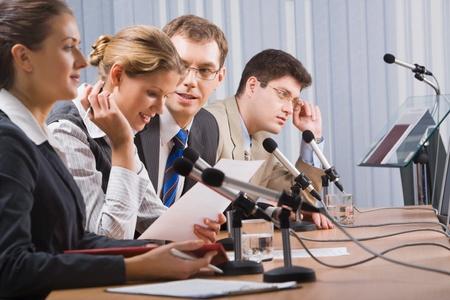 conferentie: Foto van zaken man zitten aan de tafel en te praten tijdens een conferentie  Stockfoto