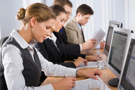 Portrait of confident people sitting in a line in front of monitors and looking at camera Stock Photo - 8393955