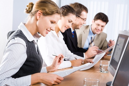 study table: Photo of business people reading a text in the classroom
