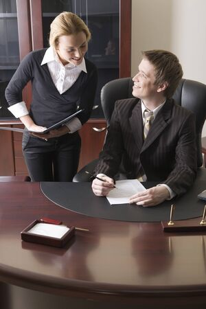 Pretty girl with the folder in her hands and man sitting at the table and signing the document Stock Photo - 8393899