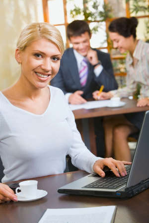 Confident business woman in white blouse sitting at the table with cup, laptop, paper on it  photo