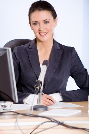 Portrait of strong woman sitting at the table and looking at camera photo