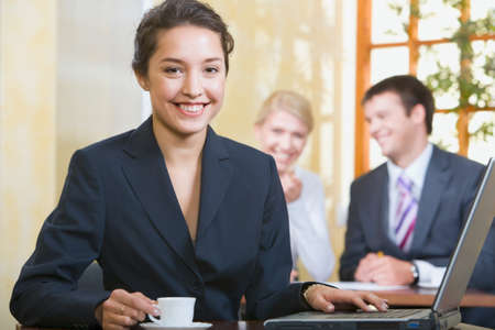 Portrait of smiling woman looking at camera on the background of two business people Stock Photo - 8393889
