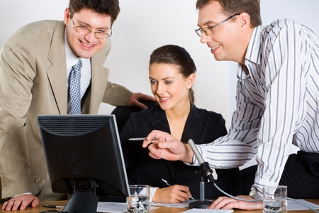 Portrait of three business people looking at monitor of laptop photo
