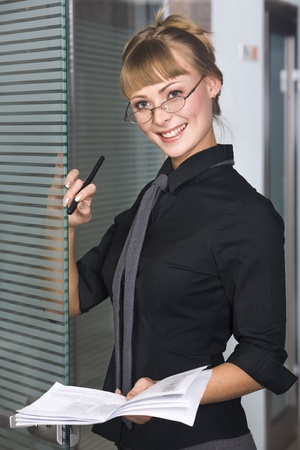 svelte: Svelte young woman in black business blouse is holding business plan in her hand Stock Photo