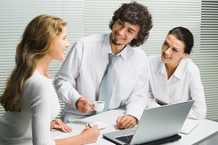 Group of three young business people gathered together around the laptop discussing an interesting idea photo