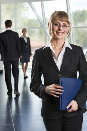 Smiling Caucasian businesswoman in eyeglasses with blue paper case in her hands and two walking businesspeople on the background photo