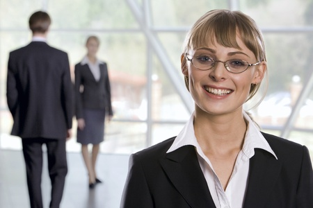 Smiling Caucasian businesswoman in eyeglasses and two walking businesspeople on the background Stock Photo - 8393874