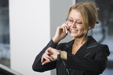 Beautiful blond young woman in black suit is speaking on her cell phone and noting the time photo