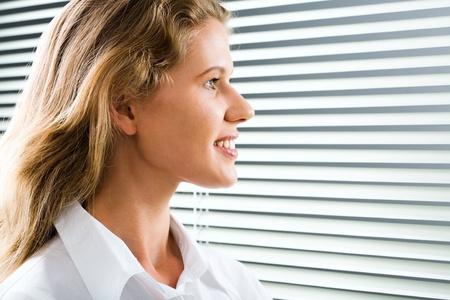 Young beautiful woman looking through white jalousie photo