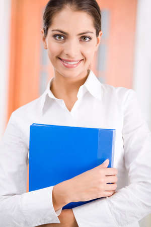 Successful smiling woman holding the blue folder on a background of door photo