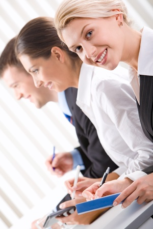 Portrait of pretty woman with friendly smile on the background of business people Stock Photo - 8393825