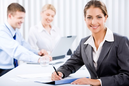 associate: Portrait of happy business woman sitting at the table on the background of her coworkers Stock Photo