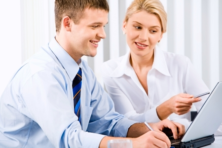 interacting: Business woman is explaining the correct way of analysis to her colleague pointing at the monitor of laptop Stock Photo