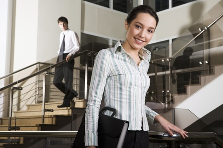 downstairs: Pretty young business holding document case in her hand going downstairs and business man going downstairs on the background