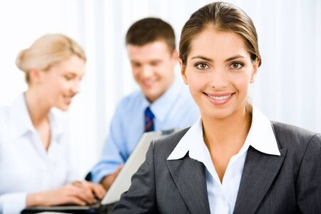 Young beautiful woman is holding a document on the background of business people photo