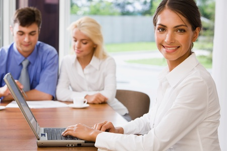 Young successful smiling woman in a working environment on a background of her colleagues photo