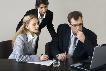 Worried young businessman sitting at the table and two businesswomen behind him looking at the laptop photo