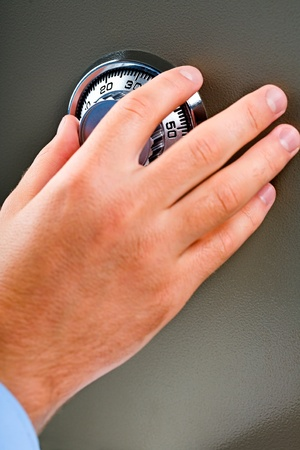 Male hand picking  a combination lock on the safe. photo