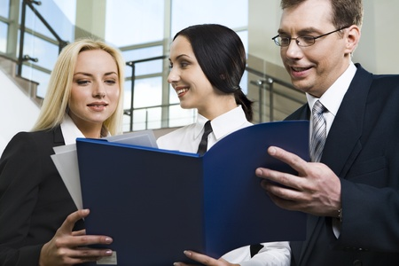 Smiling young woman showing documents and her colleagues attentively reading them photo