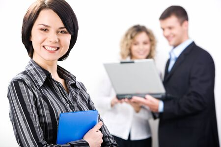Portrait of attractive consultant with friendly smile on the background of two colleagues  photo