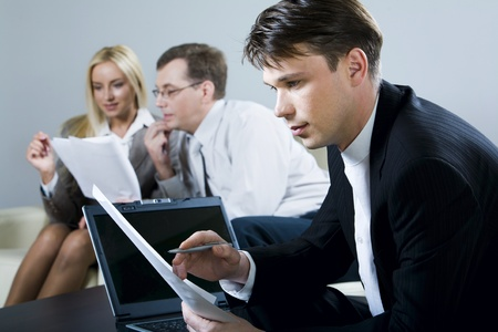 Portrait of serious man reading a document with open laptop and two reading businesspeople on the background photo