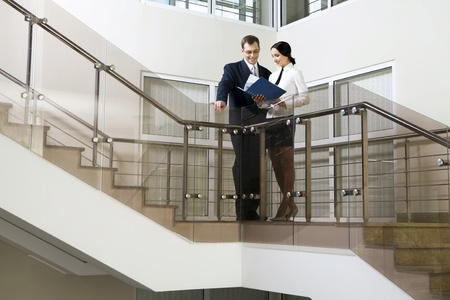 Young cute Hispanic businesswoman showing documents to her colleague on stairs in the office building Stock Photo - 8394406