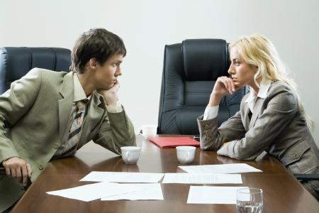 Zwei Geschäftsleute an einander gegenseitig sitzen am Tisch mit Cups, Glas Wasser, Papier-Fall und übersät Dokumente auf es und leere schwarz Stühle um ihn herum hart starrte
