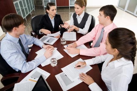 Business administration: Gran grupo de j�venes empresario reunidos alrededor de la laptop debatiendo la cuesti�n interesante Foto de archivo