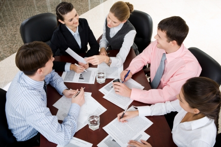 administrative: Gran grupo de j�venes empresario reunidos alrededor de la laptop debatiendo la cuesti�n interesante Foto de archivo