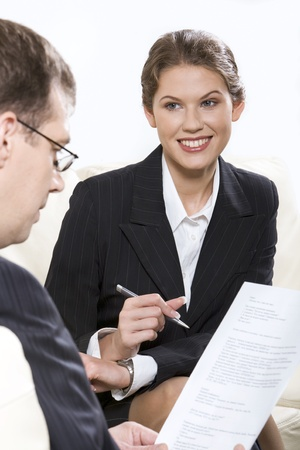 직업: Smiling businesswoman with pan in her hand sitting on the sofa and businessman sitting near by reading the document
