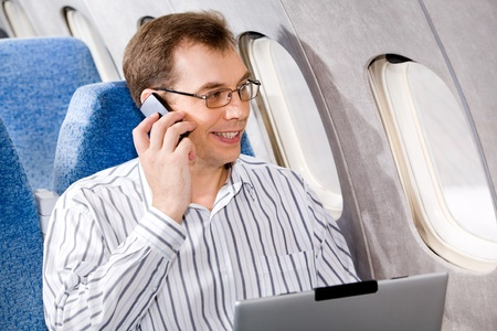 Portrait of business man calling by phone in the airplane photo