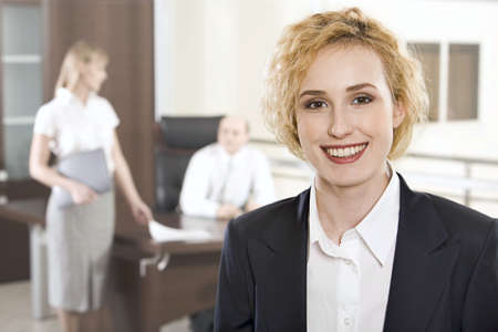 positivist: Portrait of pretty smiling businesswoman in the office and two businesspeople on the background