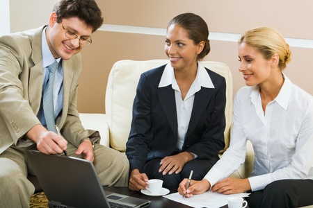 Boss is explaining the correct way of analysis to his people in working environment photo