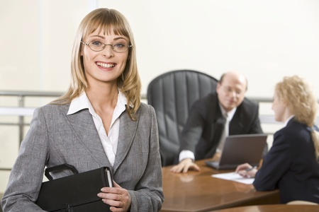 positivist: Portrait of blond smiling businesswoman holding black paper case in her hands and two businesspeople on the background Stock Photo