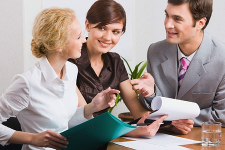 Group of three young business people are discussing new working plan in the office photo