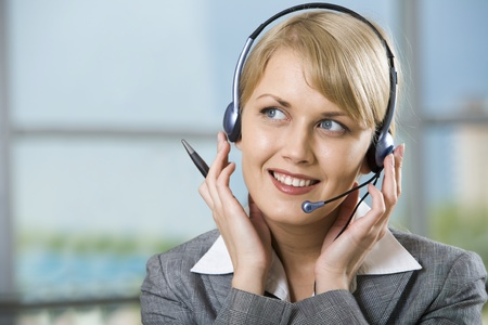 Portrait of beautiful smiling blond businesswoman in gray suit touching headset  photo
